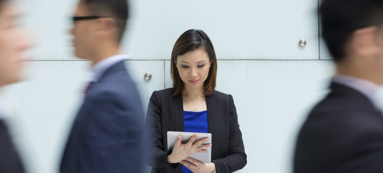 Asian businesswoman using tablet surrounded by people rushing past